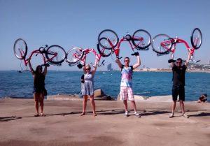 cuatro personas cargando sus biciletas en la playa